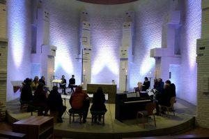 Gemeindes versammelt sich im Altarraum mit Liedern und Instrumenten.